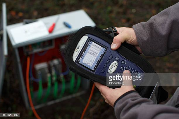 A Ziggo NV technician holds a DSAM digital service activation meter manufactured by JDS Uniphase Corp beside a fiber optic cable box in this arranged...