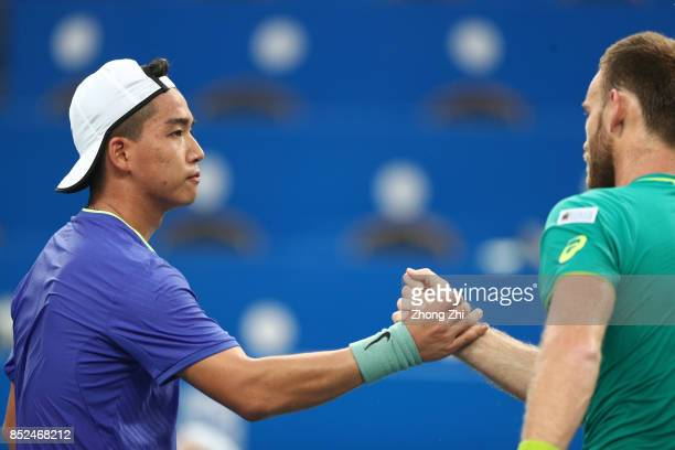 Zihao Xia of China shakes hand with Michael Venus of New Zealand after the match during Qualifying first round of 2017 ATP Chengdu Open at Sichuan...