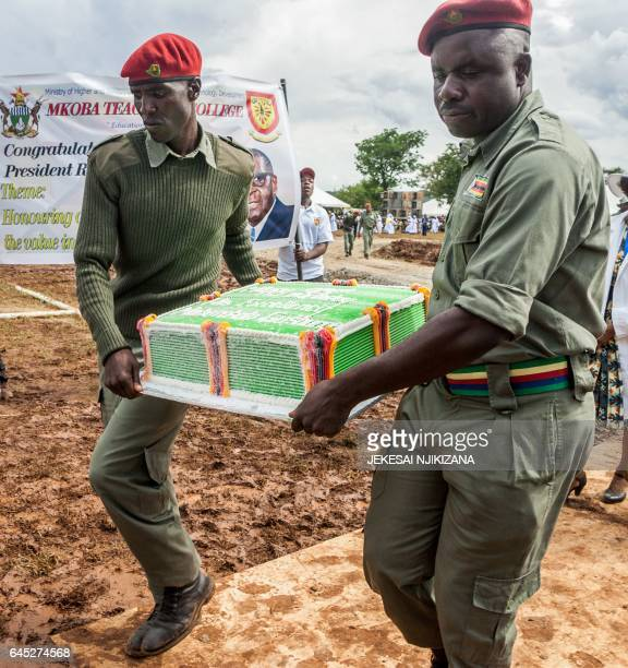 Zimbabwe African National Union Patriotic Front party youth wing members carry a 93kg icecream cake during the 93rd birthday celebrations of the...