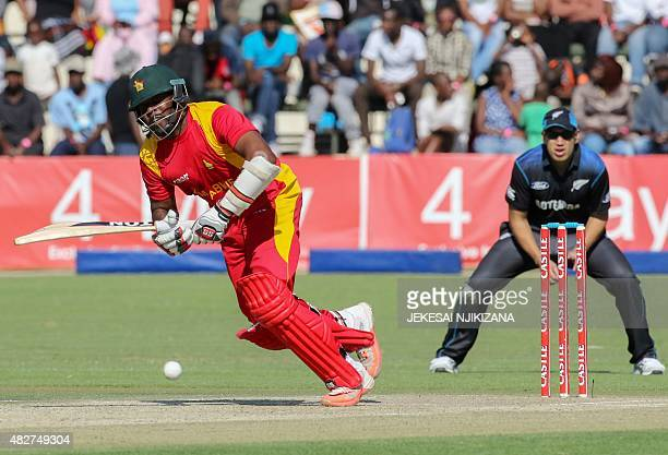 Zimbabwe batsman Hamilton Masakadza plays a shot as New Zealand's Ross Taylor looks on during the first game in a series of three One Day...