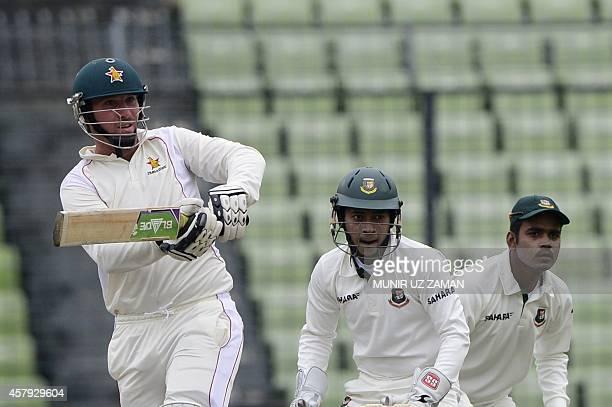 Zimbabwe cricket captain Brendan Taylor plays a shot as the Bangladesh cricket captain Mushfiqur Rahim and Shamsur Rahman look on during the third...