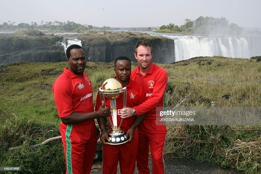 Zimbabwe cricket players Hamilton Masakadza Brendan Taylor and Prosper Utseya pose with the ICC Cricket World Cup trophy on September 30 2014 in...
