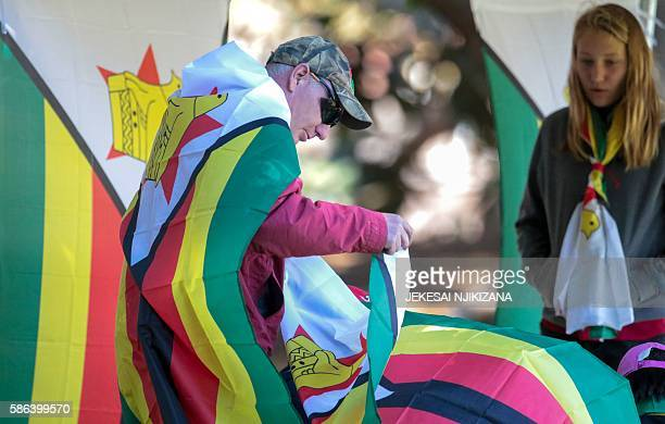 A Zimbabwe cricket supporter drapped in the national flag looks on during the first day of the second test in a series of two matches where New...