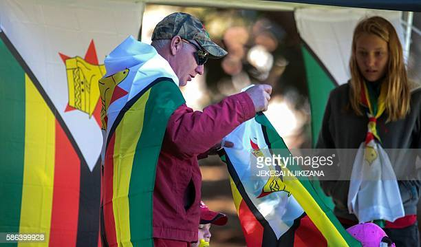 A Zimbabwe cricket supporter drapped in the national flag reacts during the first day of the second test in a series of two matches where New Zealand...