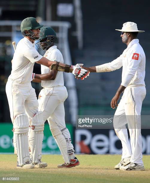 Zimbabwe cricketer Craig Ervine is congratulated by Sri Lankan cricketer Angelo Mathews after the 1st day's play of the only Test cricket match...