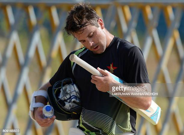 Zimbabwe cricketer Craig Ervine looks at his bat as he walks out of the nets after batting during a practice session at the Suriyawewa Mahinda...