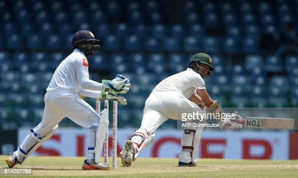 Zimbabwe cricketer Craig Ervine plays a shot as Sri Lankan wicketkeeper Niroshan Dickwella looks on during the first day of the only oneoff Test...
