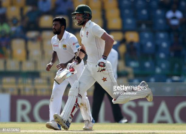 Zimbabwe cricketer Craig Ervine runs between the wickets as Sri Lankan cricketer Lahiru Kumara looks on during the first day of the only oneoff Test...