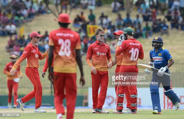 Zimbabwe cricketer Malcolm Waller celebrates with his teammates after he dismissed Sri Lankan cricketer Danushka Gunathilaka during the fourth oneday...