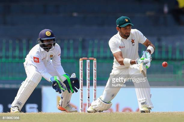 Zimbabwe cricketer Sikandar Raza plays a shot as Sri Lanka's wicket keeper Niroshan Dickwella looks on during the third day's play of the only test...