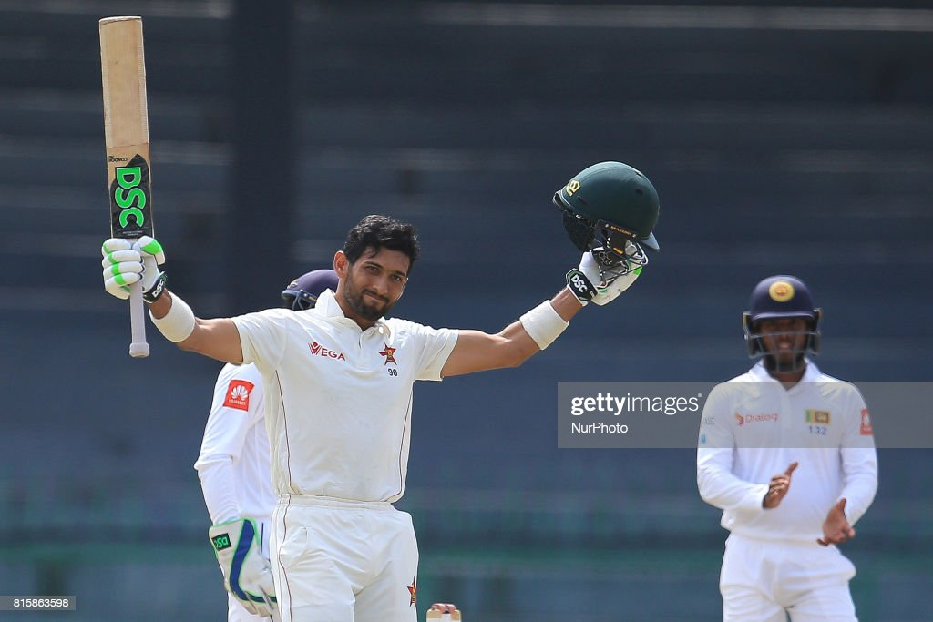 Zimbabwe cricketer Sikandar Raza(L) raises his bat in celebration after scoring 100 runs during the 4th day's play in the only Test match between Sri Lanka and Zimbabwe at R Premadasa International Cricket Stadium in the capital city of Colombo, Sri Lanka on Monday 17th July 2017