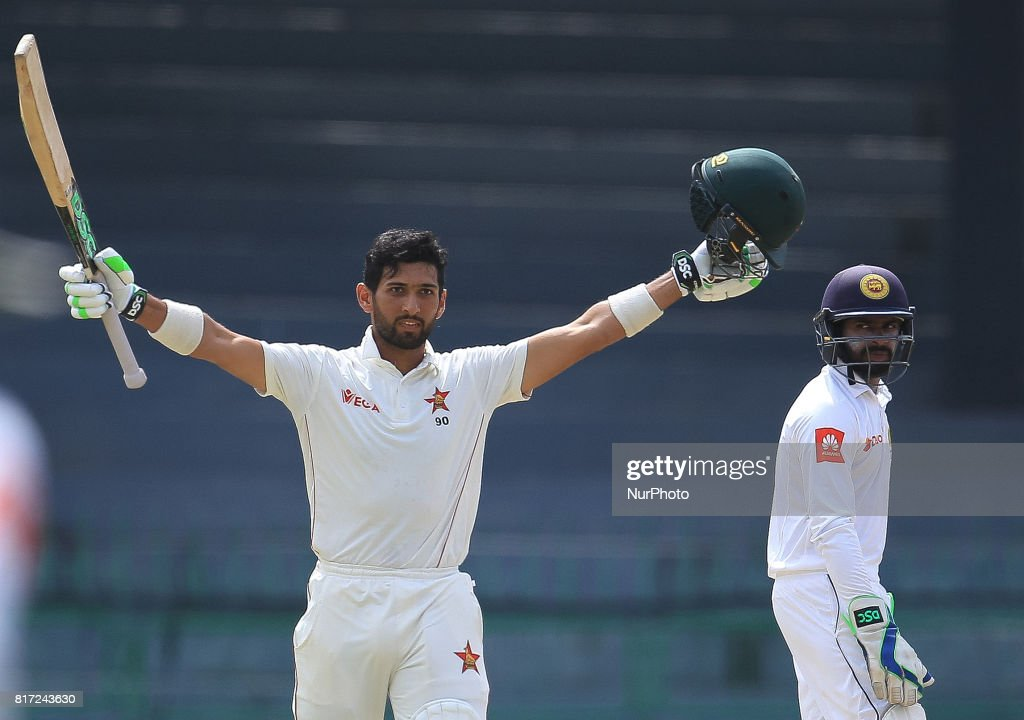 Zimbabwe cricketer Sikandar Raza(L) raises his bat in celebration after scoring 100 runs as Sri Lanka's wicket keeper Niroshan Dickwella(R) looks on during the 4th day's play in the only Test match between Sri Lanka and Zimbabwe at R Premadasa International Cricket Stadium in the capital city of Colombo, Sri Lanka on Monday 17th July 2017