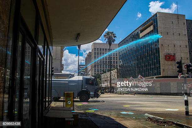 Zimbabwe police officers use a water canon during a demonstration by opposition parties against the introduction of bond notes as a currency in...