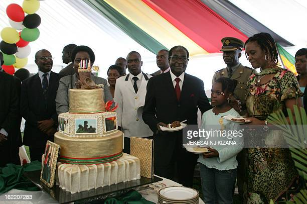 Zimbabwe President Robert Mugabe and first lady Grace Mugabe stand with the presidents birthday cake among guests on the occation of his 89th...