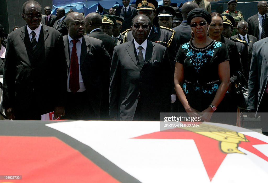 Zimbabwe President Robert Mugabe (C) and the First Lady Grace Mugabe (R) look at the flag-drapped coffin of the late vice-president John Landa Nkomo, before his burial at the National Heroes Acre, in Harare, on January 21, 2013. President Mugabe called for a peaceful election. Nkomo, 78, died at St. Anne's hospital in Harare on January 17. Responsible for overseeing financial, economic and environmental policy Nkomo, a former speaker of parliament, was seen as loyal to Mugabe. AFP PHOTO / Jekesai Njikizana