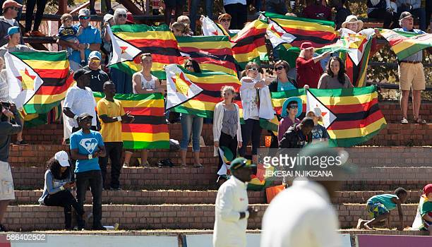 Zimbabwe supporters sing the national anthem during the first day of the second test in a series of two matches where New Zealand leads hosts...