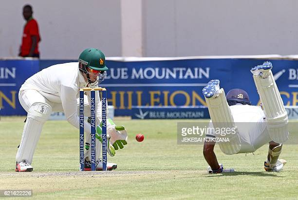 Zimbabwe wicketkeeper Peter Moor is in action as captain Rangana Herath dives to make ground during the second day of the second cricket Test match...