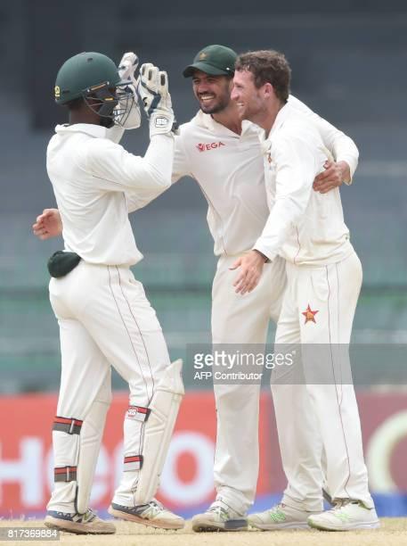 Zimbabwe wicketkeeper Regis Chakabva celebrates with captain Graeme Cremer and teammate Sean Williams after dismissing Sri Lankan cricketer Niroshan...