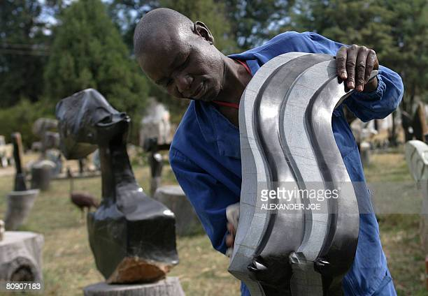 Zimbabwean artist Fanul Marliza goes on with his daliy life in Harare on April 29 2008 working on a sculpture Zimbabweans one month ago went to the...