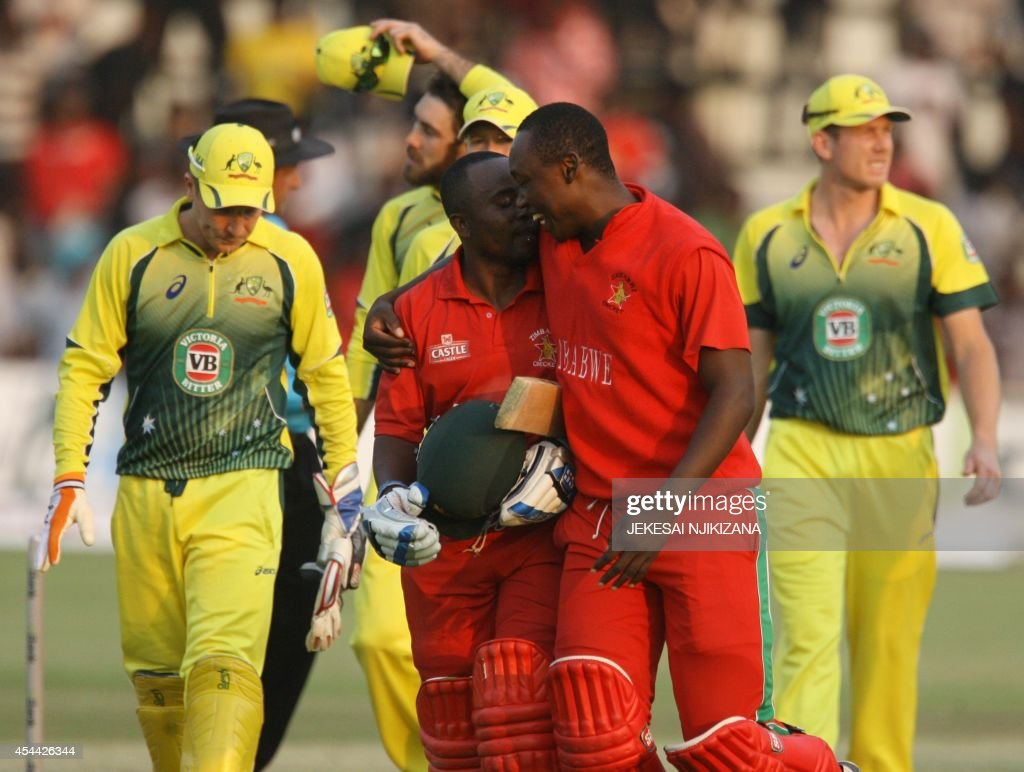 Zimbabwean batsman Prosper Utseya and his teammate Tendai Chatara celebrate their team's victory after the match between Zimbabwe and Australia in...