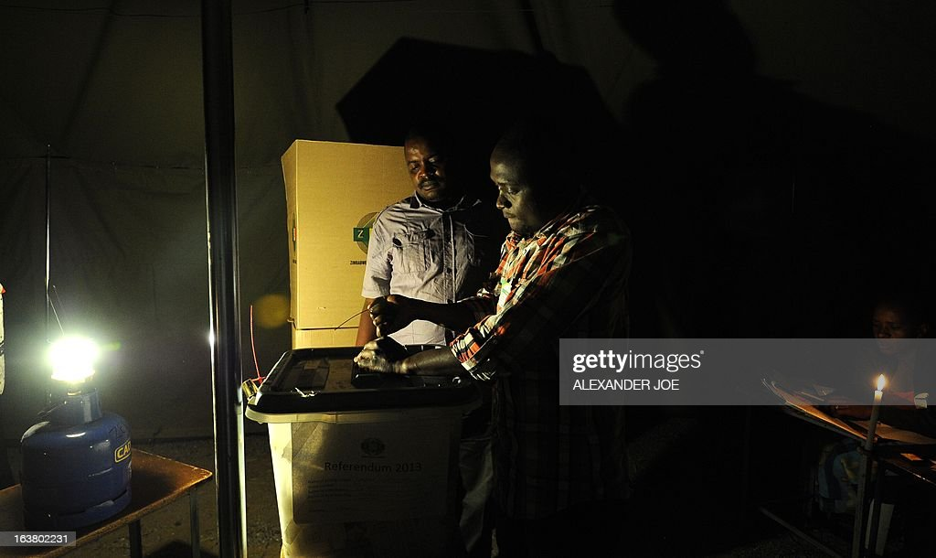 A Zimbabwean election worker seals a ballot box in a polling satation lit with candles and gas lamps in Waterfalls, a suburb of Harare, on March 16, 2013, during a referendum on a new constitution that would curb President Robert Mugabe's powers and pave the way for elections later in the year. The country's main political parties, including Mugabe's long ruling ZANU-PF, are in favor of the proposed changes to the law, making the simple majority needed for a 'yes' vote a near certainty.