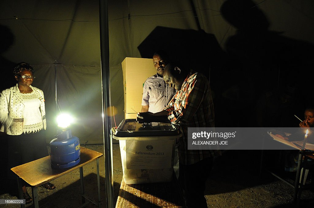 Zimbabwean election workers seal ballot boxes in a polling satation lit with candles and gas lamps in Waterfalls, a suburb of Harare, on March 16, 2013, during a referendum on a new constitution that would curb President Robert Mugabe's powers and pave the way for elections later in the year. The country's main political parties, including Mugabe's long ruling ZANU-PF, are in favor of the proposed changes to the law, making the simple majority needed for a 'yes' vote a near certainty.