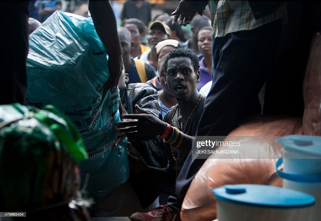 Zimbabwean migrants unload their belongings from a truck upon their arrival in Harare on April 22 after fleeing xenophobic violence in South Africa...