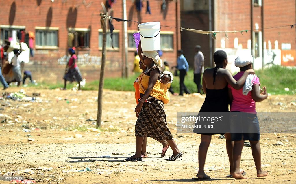 Zimbabwean mothers carry water home in Mbare township on March 17, 2013 as life goes back to normal a day after voting for a new constitution that would curb President Robert Mugabe's powers and pave the way for elections later in the year. The country's main political parties, including Mugabe's long ruling ZANU-PF, are in favor of the proposed law changes, making the simple majority needed for a 'yes' vote a near certainly.