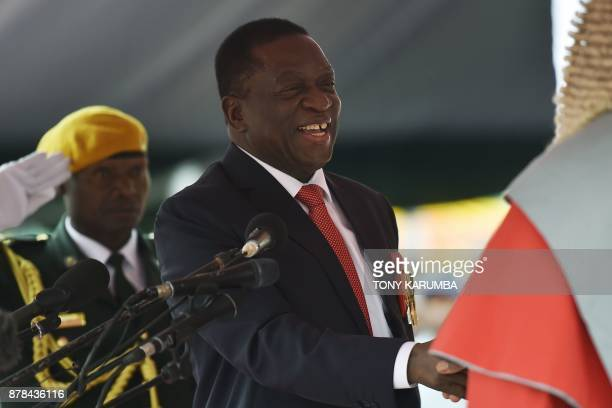 Zimbabwean new interim President Emmerson Mnangagwa shakes hands with Chief Justice of the Supreme Court Luke Malaba after he is officially swornin...