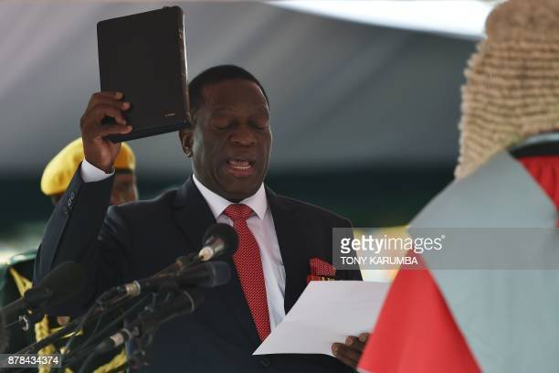 Zimbabwean new interim President Emmerson Mnangagwa takes the oath of office before Chief judge of the Supreme Court Luke Malaba as he is officially...