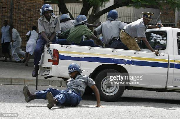 A Zimbabwean police officer falls from a police pickup truck while trying to disperse doctors and nurses demonstrating in Harare on December 3 2008...