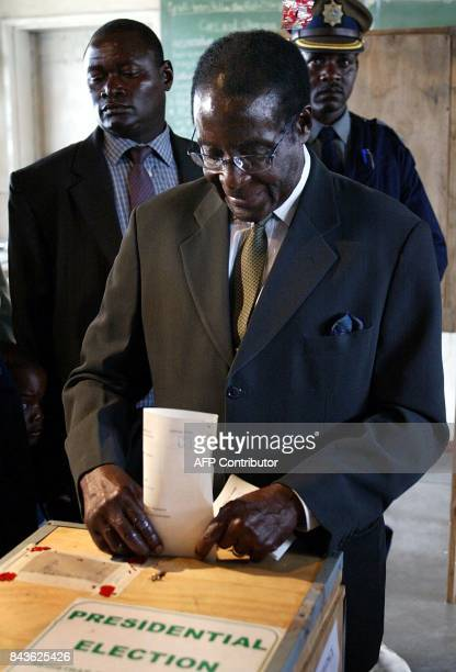 Zimbabwean President Robert Mugabe flanked by security casts his vote 09 March 2002 at a Harare polling station on the first day of two days of...
