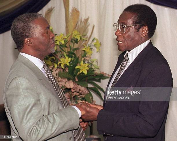 Zimbabwean President Robert Mugabe greets South African deputy President Thabo Mbeki at the VIP lounge at the Bulawayo station 12 December Mbeki is...