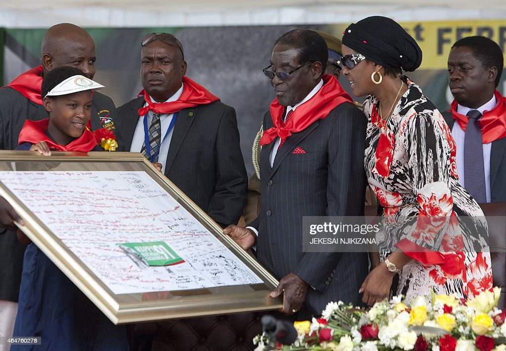 Zimbabwean President <a gi-track='captionPersonalityLinkClicked' href=/galleries/search?phrase=Robert+Mugabe&family=editorial&specificpeople=214676 ng-click='$event.stopPropagation()'>Robert Mugabe</a> (C) receives a signed gift next to lady <a gi-track='captionPersonalityLinkClicked' href=/galleries/search?phrase=Grace+Mugabe&family=editorial&specificpeople=2893817 ng-click='$event.stopPropagation()'>Grace Mugabe</a> (2nd R) on February 28, 2015 during the celebration of Mugabe's 91st birthday in Victoria Falls. Mugabe celebrated his 91st birthday with a lavish million dollar bash that was slammed by the opposition as 'obscene' in a country wracked by poverty.The extravagance of Mugabe's birthday parties are a subject of annual controversy in Zimbabwe.