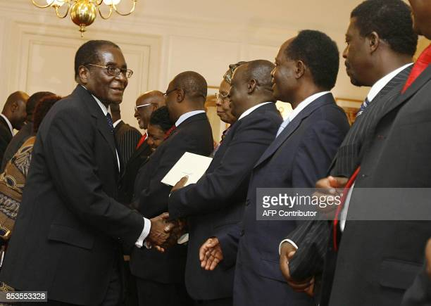 Zimbabwean President Robert Mugabe shakes hand with newly sworn in Ministers and Deputies for a new inclusive government at state house in Harare on...