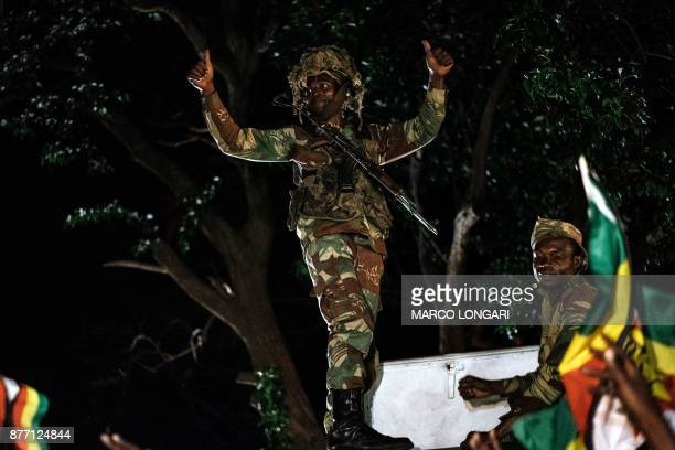 A Zimbabwean soldier gesture as people greet and celebrate after the resignation of President Mugabe on November 21 2017 Zimbabwe army chief General...