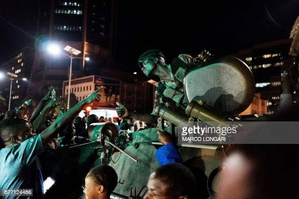 A Zimbabwean soldier sitting in tank gestures as people greet and celebrate after the resignation of President Mugabe on November 21 2017 Zimbabwe...