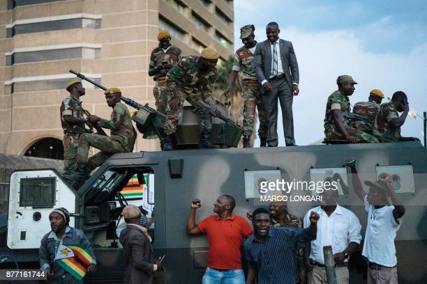 TOPSHOT Zimbabwean soldiers are celebrated by citizens in the streets in Harare on November 21 2017 after the resignation of Zimbabwe's president...