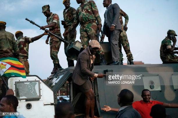 Zimbabwean soldiers are celebrated by citizens in the streets in Harare on November 21 2017 after the resignation of Zimbabwe's president Robert...