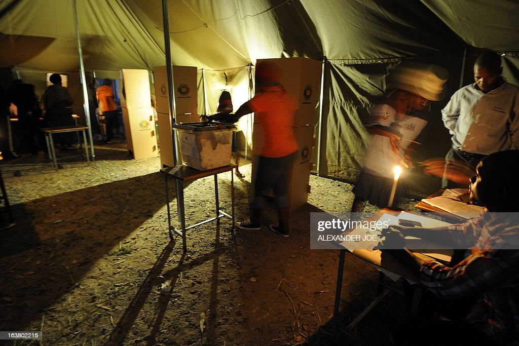 Zimbabwean voters cast their votes in a polling satation lit with candles and gas lamps in Waterfalls, a suburb of Harare, on March 16, 2013, during a referendum on a new constitution that would curb President Robert Mugabe's powers and pave the way for elections later in the year. The country's main political parties, including Mugabe's long ruling ZANU-PF, are in favor of the proposed changes to the law, making the simple majority needed for a 'yes' vote a near certainty. AFP PHOTO / ALEXANDER JOE