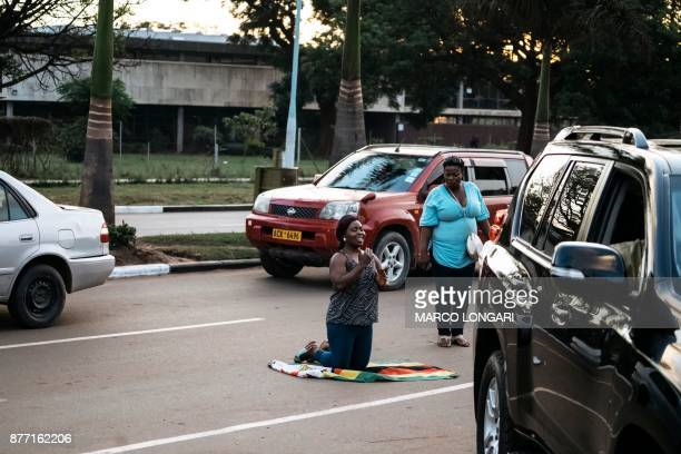 Zimbabwean woman kneels on the national flag of Zimbabwe in a street in Harare on November 21 2017 after the resignation of Zimbabwe's president...