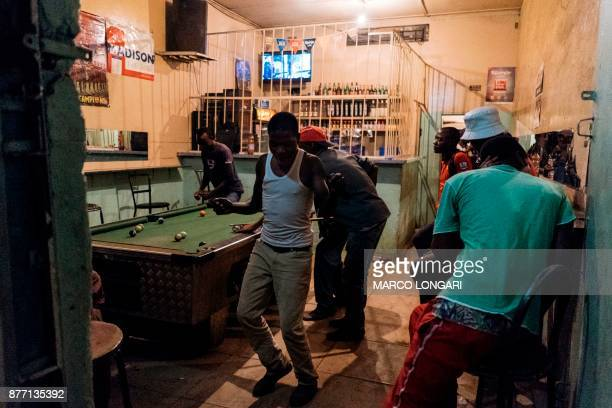 Zimbabweans celebrate in a bar as they play billiards in the township of Mbare in Harare after the resignation of President Robert Mugabe on November...