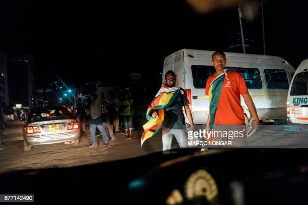 Zimbabweans celebrate in the streets in Harare on November 21 2017 after the resignation of Zimbabwe's president Robert Mugabe Car horns blared and...