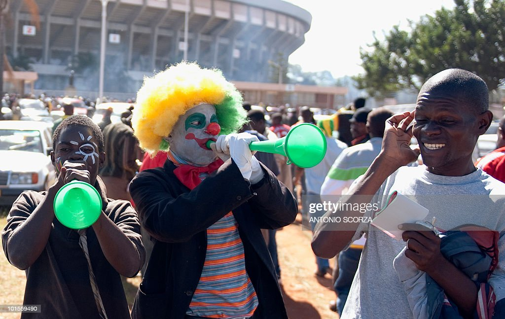 Zimbabweans football fans play the vuvuz