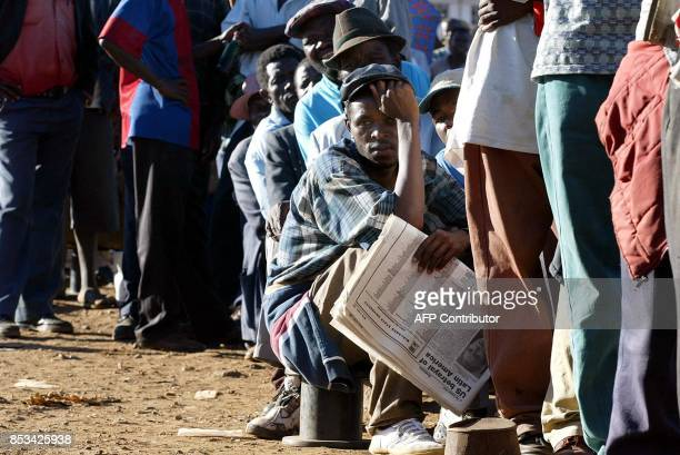 Zimbabweans queue to cast their vote 10 March 2002 at a Harare polling station Thousands of people remained in voting queues across Harare as night...