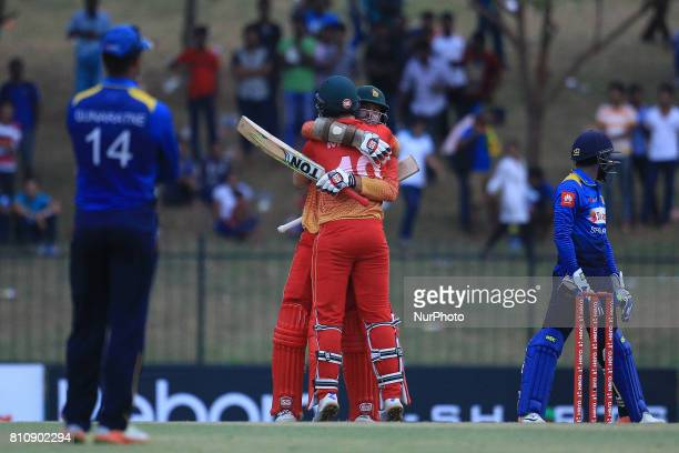 Zimbabwe's cricketer Craig Ervine hugs his teammate Peter Moor soon after scoring the winning runs during 4th oneday international cricket match...