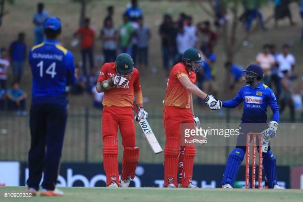 Zimbabwe's cricketer Craig Ervine shakes hands with Sri Lanka's wicket keeper Niroshan Dickwella as Zimbabwe's Peter Moor looks on after securing...