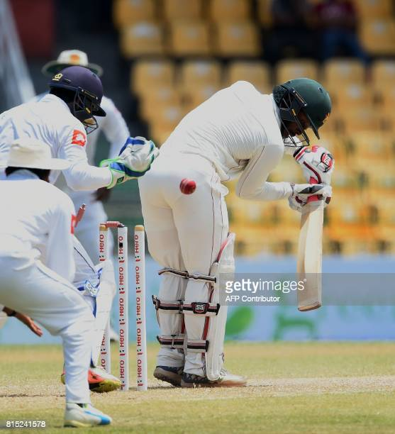 Zimbabwe's cricketer Regis Chakabva is dismissed by Sri Lankan cricketer Rangana Herath as Sri Lankan wicketkeeper Niroshan Dickwella looks on during...