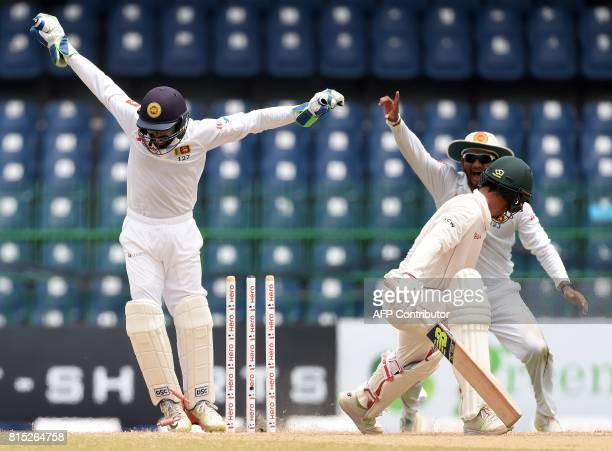 Zimbabwe's cricketer Sean Williams is dismissed by Sri Lankan cricketer Rangana Herath as Sri Lankan wicketkeeper Niroshan Dickwella and Dimuth...