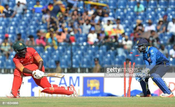 Zimbabwe's cricketer Solomon Mire gets dismissed by Sri Lankan off spinner Asela Gunaratne as wicketkeeper Niroshan Dickwella looks on during the...